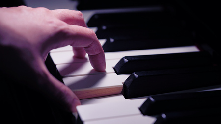 pianist: Scene of pianist hands from beside angle playing piano, Photo in vintage colors style. Selective focus.
