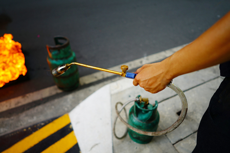 Men holding gas nozzle with blurred fire and gas tank on the ground floor, selective focus