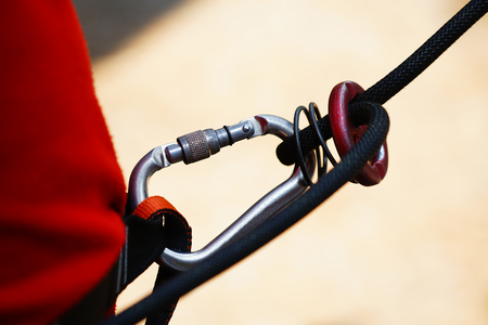 Close-up of carabiner safety hooked with the rope.