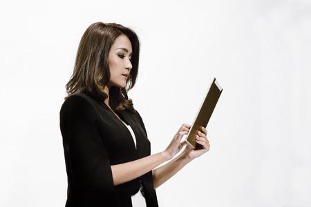 Jonge bedrijfsvrouw die op de tablet in haar hand met witte ruimte als achtergrond en exemplaar kijkt. Stockfoto