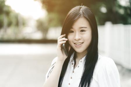 Aziatisch meisje die op de mobiele telefoon bij openlucht met gloedlicht spreken.