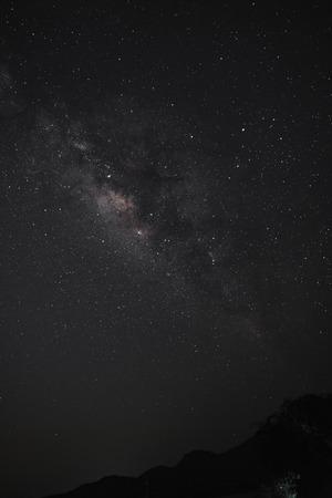 De Melkweg boven de bergen in verticale weergave. Lange belichtingsfoto. Stockfoto