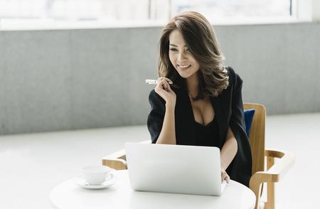 Jonge onderneemsterzitting op de stoel en het werken met laptop.