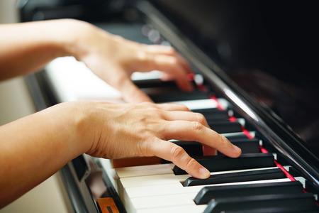 Scène van pianisthanden van naast hoek het spelen piano. Selectief gericht. Stockfoto