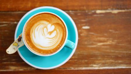 Vlakke latte kunst op de wazige houten tafel met kopie ruimte.
