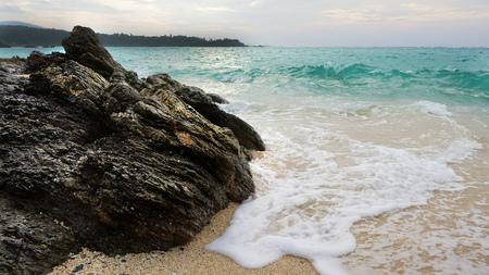 Golf en schuim van de zee op het zandstrand met rock op de voorgrond, voor zonsondergang.