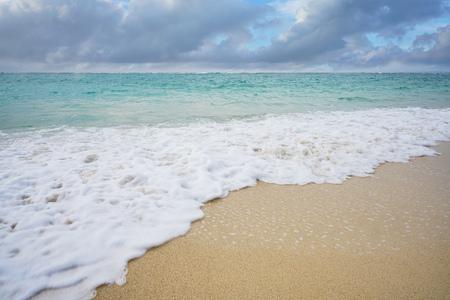 Golf van witte zee spons op het zandstrand met bewolkte hemel. Stockfoto