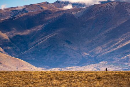Young man cycling mountain bike along the rural trail of golden grass field with mountain and blue cloudy sky as background