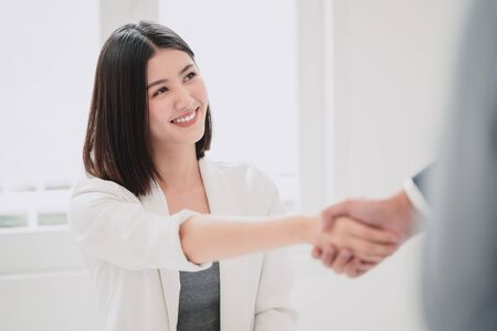 Beautiful young asian business woman smiling with triumphant of the success deal or project while shaking hand with business man with the white natural sunlight as a background.