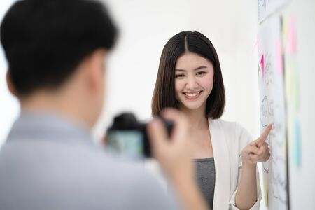 Young beautiful asian vlogger smiling with confident and pointing at the content while recording viral clip for steaming online and share on social media in the white room as a background. Stockfoto