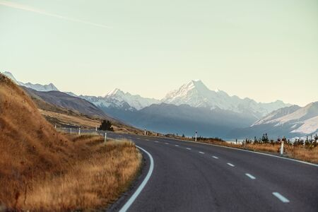 Scenic View of Mt Cook in New Zealand with soft blue sky, view from car windshield while driving along the road on ridges. Nature sightseeing view are popular for tourist for look around.