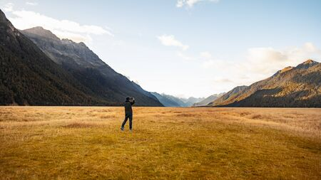 A tourist holding camera taking photo at the view point of Ellington Valley while travelling along the road trip to Milford sound, scenic of vast meadow with beautiful mountain ranges at the back with 写真素材