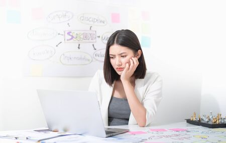Asian beautiful office worker looks stressed and frustrated while working typing and solving problem on the laptop in the white meeting room, concept stress at work.