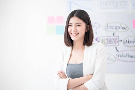 Portrait of young beautiful and confident business woman smiling and standing in front of meeting board or planning chart give the positive attitude of work in the white meeting room as a background.