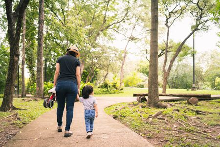Scene from behind of young asian mother and her child toddler girl exploring the park with excitement while the mother holding a mini bike in warm sunlight tone, concept mother and child in the park. Stockfoto