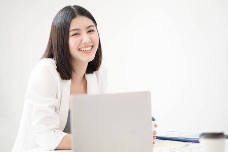 Young asian woman employee smiling with happiness and confident while looking toward camera with a white meeting room background, concept happy working environment. Stockfoto