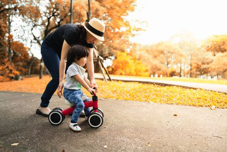 Cute 2 years old asian toddler learn how to ride a bike helped and protected by her mother in the autumn color season park, concept outdoor family activity time. Banco de Imagens