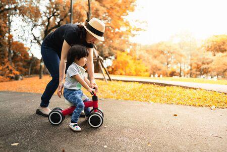 Un mignon bambin asiatique de 2 ans apprend à faire du vélo aidé et protégé par sa mère dans le parc de la saison des couleurs d'automne, concept d'activité familiale en plein air.