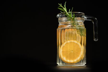 a glass jar of orange and rosemary infused water or sparkling water with ice cube at the bottom for refreshment on black background with copy space at the left