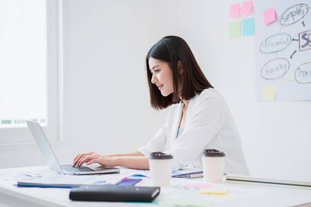 Beautiful young asian business woman looks happy and concentrate working with her laptop while sitting in the white office in good natural sunlight, efficient working environment atmosphere concept. Stockfoto