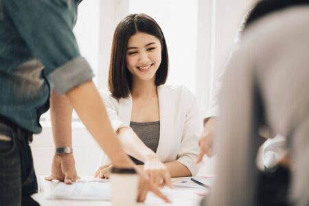 Young beautiful asian business woman smiling and satisfied with the plan and pointing at the project chart or planning with colleague in the white meeting room.
