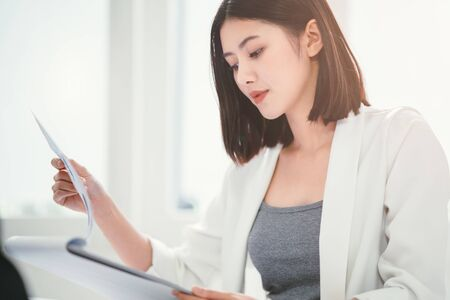 Close up of young beautiful asian businesswoman concentrate or reading on the content or checking project clipboard before presentation in the white room as a background with natural sunlight.