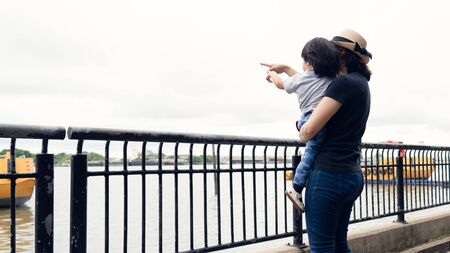 Asian mother and her toddler girl boy pointing out to the big boats in the river while answer the question from her daughter, learning and explore the environment together, happy family outing time. Stockfoto