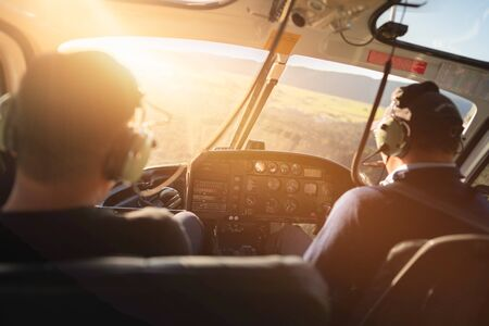 Scene of helicopter cockpit from the rear side which have two pilots at the front seat, while flying helicopter tours in sunny light atmosphere, helicopter tours is the famous activity in NewZealand.