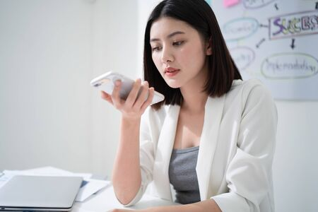 Young beautiful asian business woman using voice texting or voice communication on mobile phone while sitting in the white office working room with many strategic planning chart as a background. Stockfoto