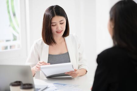 Beautiful asian business woman is reading the resume and gives the interview as a human resource for company recruitment with an interviewee in a white office as a background.