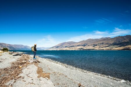 Tourist admires the view while stand next to Lake wanaka Boundary Creek with background of blue sky and rocky mountain with copy space.