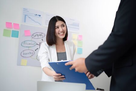 A beautiful young Asian business woman is smiling, happy, and satisfied after receiving a presentation file or summarizing plans from colleagues with a white meeting room in the background.