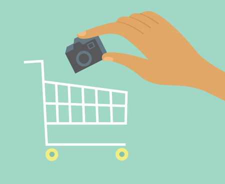 adds: Hand adds camera to a shopping cart Online shopping concept