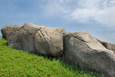 straight path: Rock with blue sky and grass Stock Photo