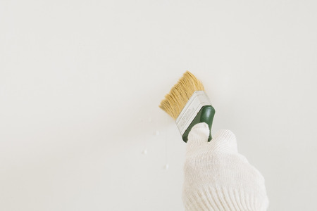 white glove: the brush in his hand in a white glove against a light wall