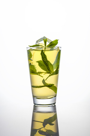 pellucid: iced tea and mint in a tall glass on white background with reflection Stock Photo