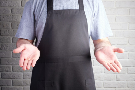 man in black apron hand closeup on background of brick wall Stockfoto