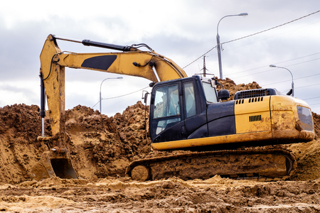 yellow excavator working on sand, the road construction in cloudy weather