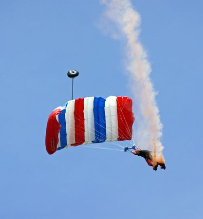 Parachute  parachutist  sky diver against blue sky with smoke and colorful parachute coming down to land on earth photo