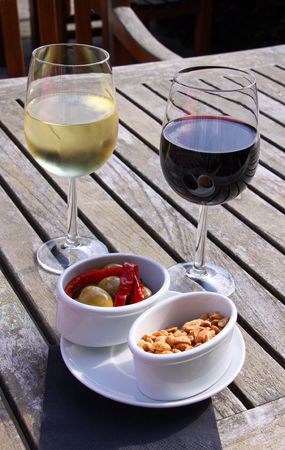 Glasses of red and white wine with olives and peanuts Stock Photo