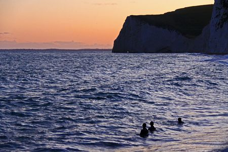 Swimmers  divers in the sea at dusk in the bay of Durdle Door on the Jurassic Coast, South England photo