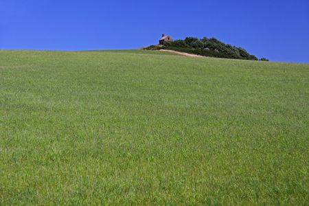 dwell: Rural farm barn building in a sloped green field with blue sky Stock Photo