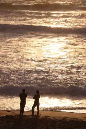 A couple talking at sunset on the sea shore at the famous surfing beach Fistral Bay, Cornwall, UK photo