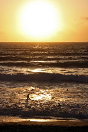 Silhouetted people in the sea at the famous surfing beach Fistral Bay, Cornwall, UK photo