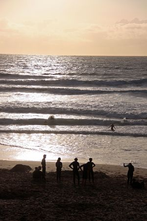 Silhouetted people, swimmers and surfer on the beach at the famous surfing Fistral Bay, Cornwall, UK photo