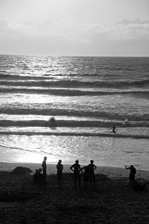 Silhouettes of swimmers  surfers and people watching the sun set and sea scape at the famous surfing beach Fistral Bay, Cornwall, UK photo