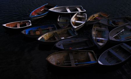 Old, unused, colorful, wooden rowing  fishing boats moored in a cove photo