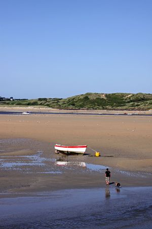 View of fishing boat  yacht at low water tide and blue sky at Padstow, Cornwall, UK photo