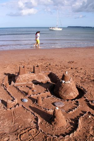 Sand castle on a red sand beach in Devon, UK and yacht and sea view photo