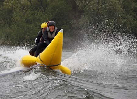 Young woman on a banana boat and splashing water